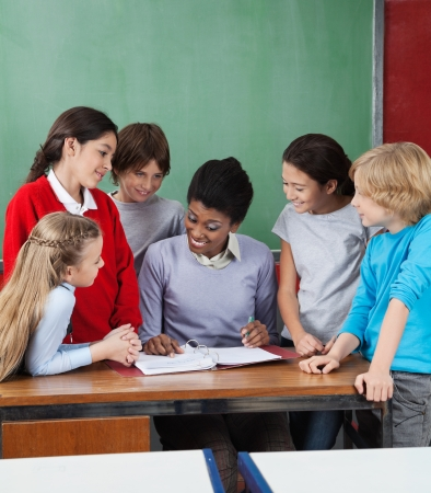 Young female professor teaching group of students at desk in classroom Stock Photo - 23745202