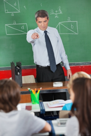 male teacher: Angry mature male teacher pointing at schoolboy in classroom Stock Photo