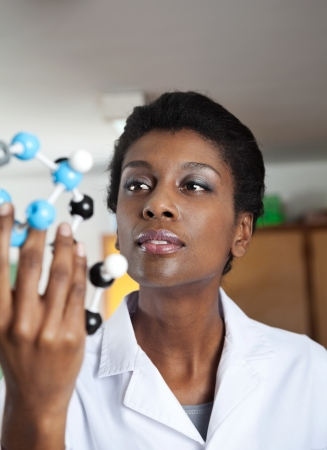 high school teacher: African American female teacher looking at molecular structure in science lab