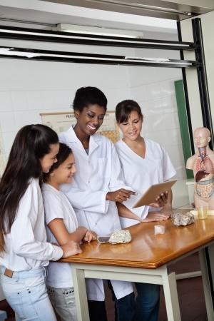 bata de laboratorio: Profesor afroamericano que usa la tableta digital, al tiempo que explicó a los estudiantes en el escritorio en el laboratorio de ciencias Foto de archivo