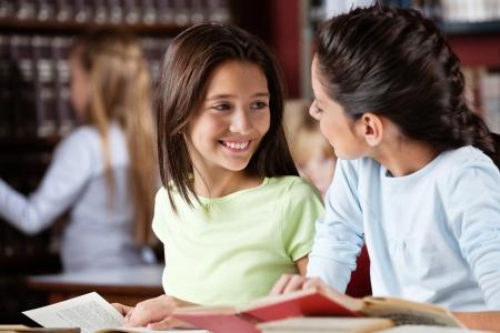 niños estudiando: Colegiala feliz que mira la amiga mientras estudiaba en la biblioteca