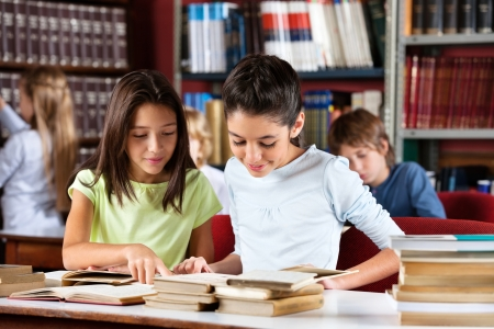 study room: Little schoolgirls reading book together while sitting at table in library with classmates
