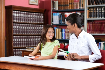 Young female librarian looking at schoolgirl while sitting with books at table in library Stock Photo - 23745279