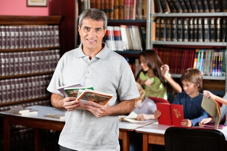 male teacher: Portrait of confident male librarian holding books while standing in library with students studying