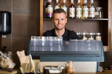 coffee house: Portrait of smart male bartender at counter in cafe Stock Photo