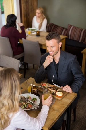 Businessman having food with female colleague at restaurant photo