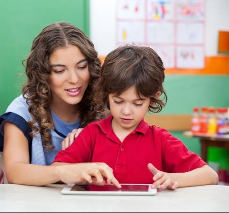 salle de classe: Jeune professeur enseigner aux �l�ves � utiliser la tablette num�rique en classe