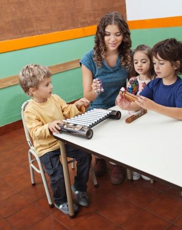 乳幼児: 若い先生の教室で子供たちと楽器演奏 写真素材