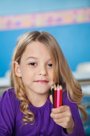 elementary students: Portrait of cute girl holding bunch of color pencils in preschool Stock Photo