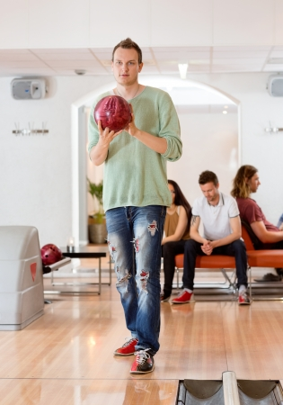 Full length of young man holding ball with people in background at bowling club photo