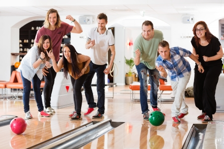 bowling alley: Young friends bowling while people cheering in club