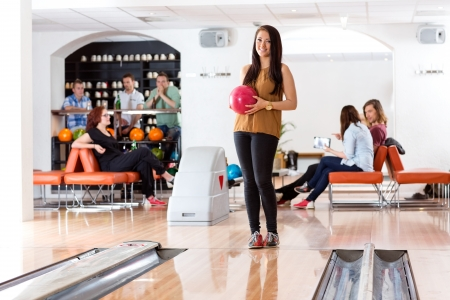 bowling ball: Full length of beautiful young woman holding bowling ball with people in background Stock Photo