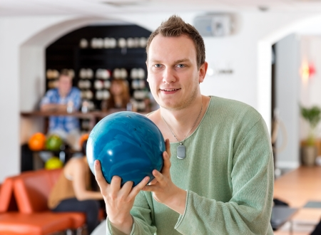 bowling alley: Portrait of young man holding blue bowling ball with people in background at club