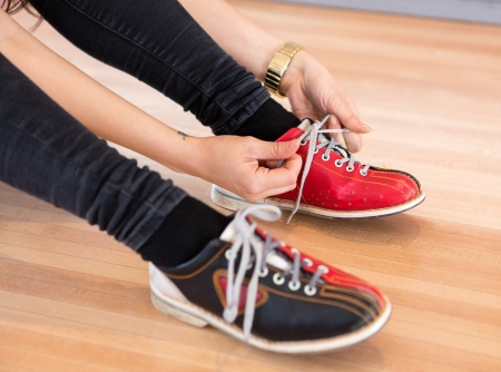 Low section of young woman tying shoe lace on wooden floor in club photo