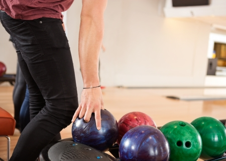 Midsection of young man choosing bowling ball from rack in club photo