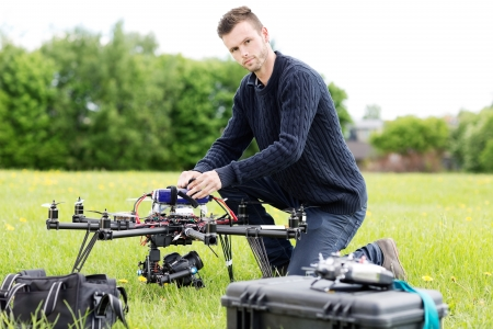 Portrait of confident young engineer preparing spy drone in park