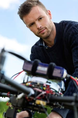 Closeup portrait of young engineer with UAV helicopter in park photo