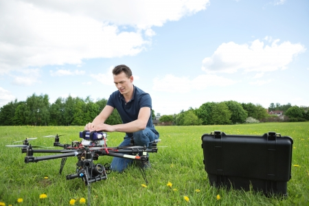 Young engineer crouching while fixing photography UAV in park photo