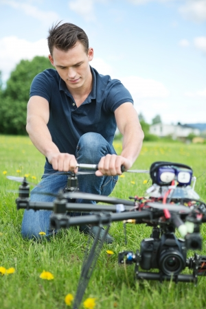 Young engineer crouching while fixing propeller of UAV drone in park photo