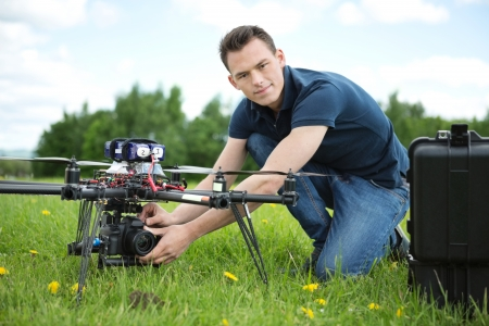 Portrait of confident young engineer setting camera on photography drone in park photo