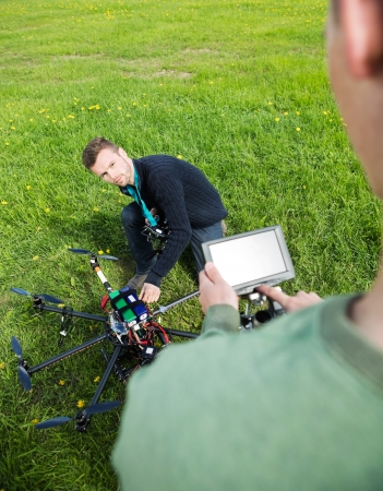 Young engineer fixing UAV helicopter with colleague adjusting screen in park photo