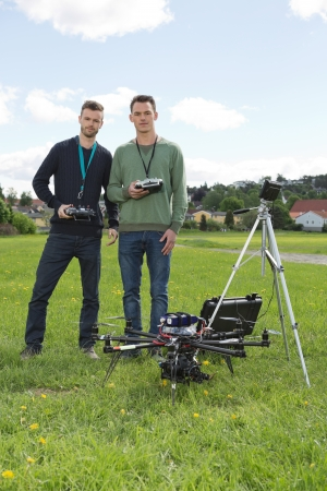 Portrait of confident engineers holding remote controls of UAV helicopter at park photo