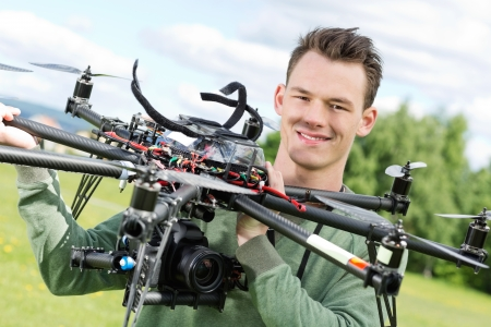 Portrait of confident male technician holding UAV octocopter in park photo
