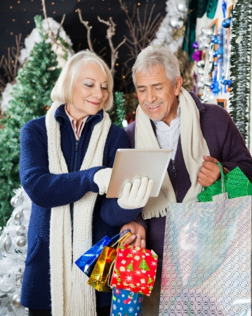 Senior couple with shopping bags using digital tablet together at Christmas store photo