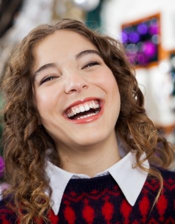 bureta: Primer retrato de mujer joven alegre que ríe en la tienda de Navidad Foto de archivo