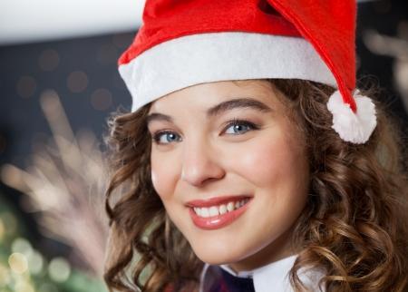 bureta: Primer retrato de mujer joven y hermosa con el sombrero de Santa en la tienda de Navidad Foto de archivo