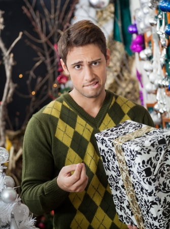 holding a christmas ornament: Portrait of young man with Christmas gift biting lips in store Stock Photo