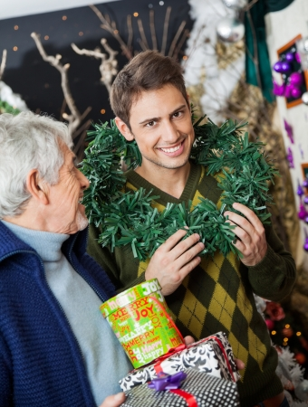 Portrait of happy man holding wreath around neck standing with father at Christmas store photo