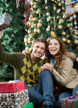 Happy young couple with presents sitting on floor in Christmas store photo
