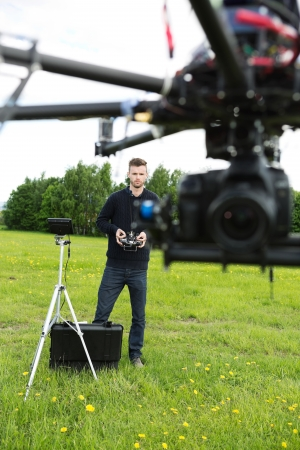 UAV octocopter flying while male engineer operating it in the park photo