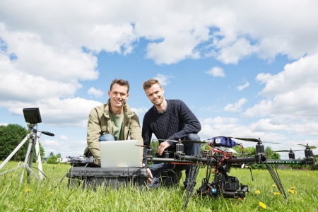 troubleshoot: Portrait of men using laptop next to UAV octocopter and tripod against cloudy sky