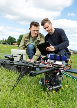 Young male technicians discussing over laptop and digital tablet by UAV helicopter in park photo