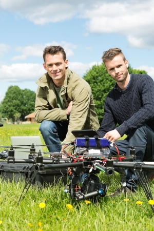 Portrait of male technicians with laptop and digital tablet by UAV at park photo