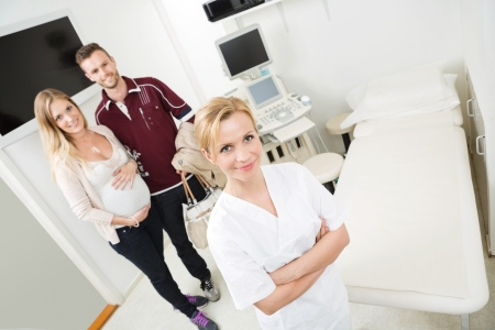 High angle view of young doctor and expectant couple standing in examination room photo