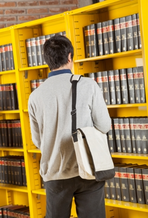 Rear view of male student carrying bag while standing against bookshelves in college library photo