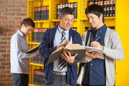 Mature male librarian assisting student in college library photo