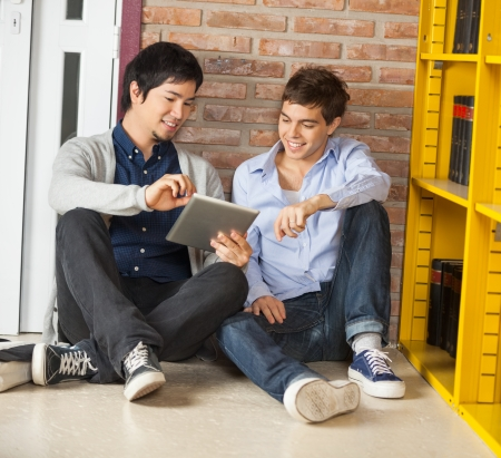 bookshelf digital: Happy male students using digital tablet together while sitting by bookshelf in university library