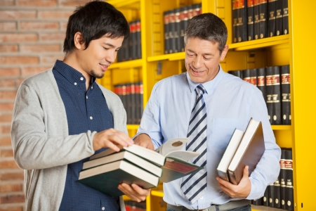 Happy male student holding books while discussing with librarian in college library photo