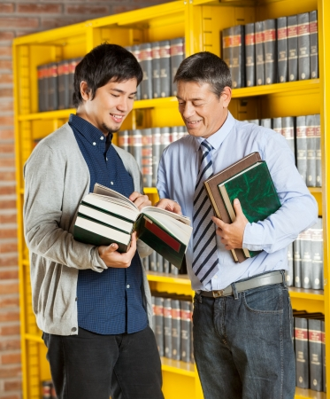 Mature male librarian holding books while explaining student in university library photo