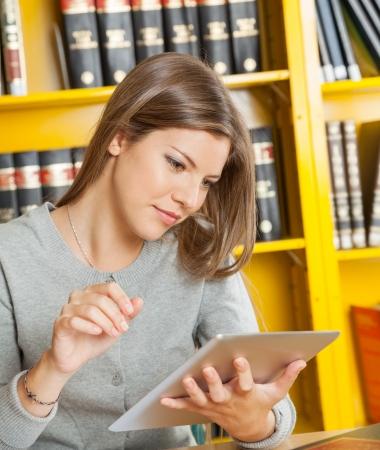 bookshelf digital: Beautiful female student with digital tablet studying against bookshelf in university library Stock Photo