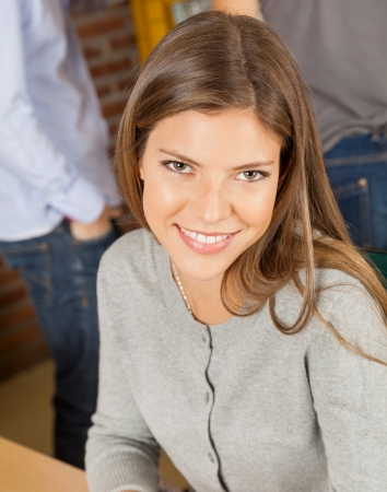 Portrait of beautiful young woman smiling with students standing in background at university library photo