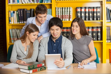 Group of multiethnic students with digital tablet studying together in college library photo