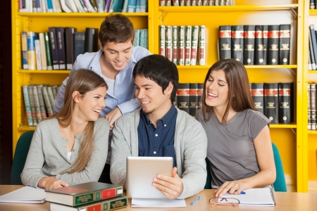 Group of happy college friends with digital tablet studying in library photo