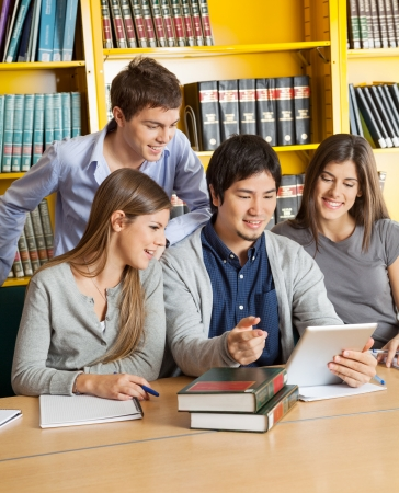 Happy multiethnic students with digital tablet discussing in college library photo