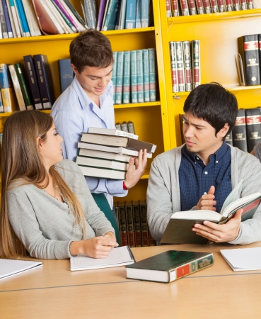 Male student carrying books while friends sitting at table in college library photo