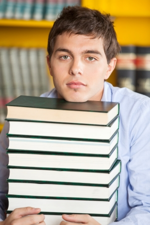 scholar: Portrait of male student resting chin on stacked books in college library Stock Photo